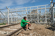 A refugee sits on the railway in front of the closed border between Greece and Macedonia.