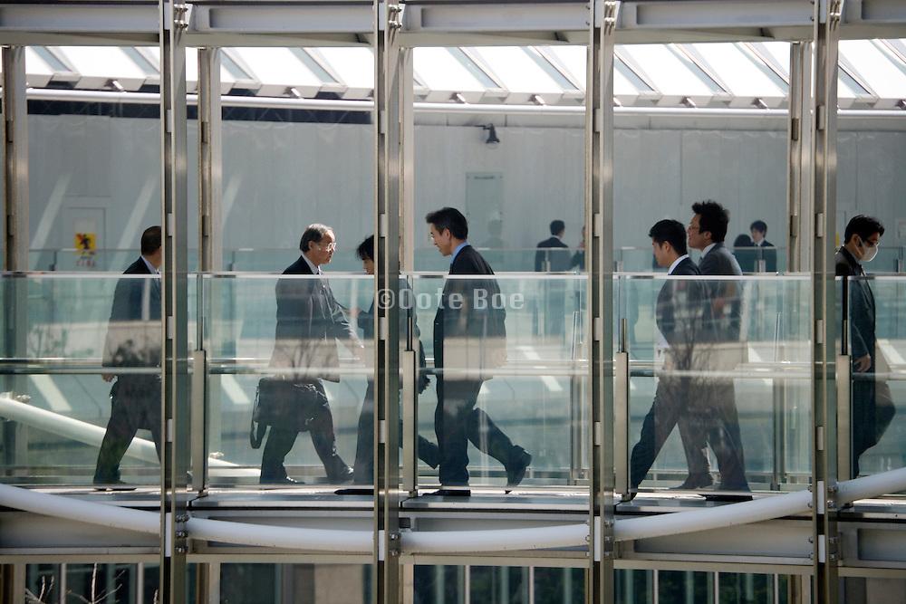Japanese businessmen walking over bridge between office buildings