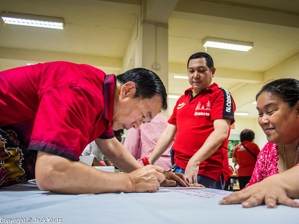 27 JULY 2013 - BANGKOK, THAILAND: Thai Red Shirts write birthday greetings for Thaksin Shinawatra on a roll of paper during a birthday party for Thaksin. The Red Shirts celebrated former Prime Minister Thaksin Shinawatra's 64th birthday with a party at Phibun Prachasan School in Bangkok. They had a Buddhist Merit Making Ceremony, dinner, cake and entertainment. Most of the Red Shirt political elite traveled to Hong Kong for a party with Thaksin. Thaksin, the former Prime Minister, was deposed by a coup in 2006 and subsequently convicted of corruption related crimes. He went into exile rather than go to jail but remains very popular in rural parts of Thailand. His sister, Yingluck Shinawatra is the current Prime Minister and was elected based on her brother's recommendation.     PHOTO BY JACK KURTZ