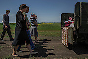 Starovarvarovka, Ukraine - May 16, 2014: Nadezhda Sanzharevskaya, 49, mourns her sister Yelena Ott, 42, at the back of a truck as her coffin is driven through farms to the cemetery for burial in the small village of Starovarvarovka, eastern Ukraine. According to Yelena Ott husband, Alexander, she was shot near a check point about three kilometers away of her home after being stopped by Ukrainian soldiers, currently under operation against pro-Russian militants in the surroundings of Kramatorsk. CREDIT: Photo by Mauricio Lima for The New York Times