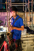 19 JANUARY 2014 - BANGKOK, THAILAND:  A mor lam saxophone player performs during a mor lam show in Khlong Tan Market in Bangkok. Mor Lam is a traditional Lao form of song in Laos and Isan (northeast Thailand). It is sometimes compared to American country music, song usually revolve around unrequited love, mor lam and the complexities of rural life. Mor Lam shows are an important part of festivals and fairs in rural Thailand. Mor lam has become very popular in Isan migrant communities in Bangkok. Once performed by bands and singers, live performances are now spectacles, involving several singers, a dance troupe and comedians. The dancers (or hang khreuang) in particular often wear fancy costumes, and singers go through several costume changes in the course of a performance. Prathom Bunteung Silp is one of the best known Mor Lam troupes in Thailand with more than 250 performers and a total crew of almost 300 people. The troupe has been performing for more 55 years. It forms every August and performs through June then breaks for the rainy season.              PHOTO BY JACK KURTZ