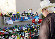 A man looks over the memorial outside the offices of congresswoman Gabrielle Giffords in Tucson, Arizona January 11, 2011. REUTERS/Rick Wilking (UNITED STATES)