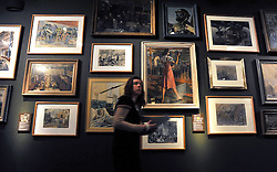 © Licensed to London News Pictures. 04/04/2012. London, UK A member of museum staff walks past a wall of paintings depicting scenes from the era. Photo call and preview for the Imperial War Museums new A Family in Wartime exhibition. The exhibition features the life on the Home Front during the Second World War, explored through the eyes of one London based family, the Allpress. Photo credit : Stephen SImpson/LNP