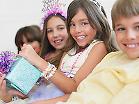 Children (7-12) sitting in row at birthday party one holding present