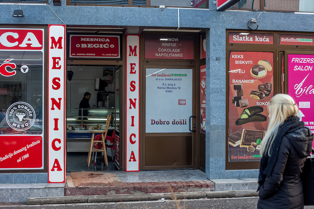 A wopman is waiting in front of a butcher beside a chocolate shop at Ilidža which is a municipality of Sarajevo Canton in central Bosnia and Herzegovina. It has a metro population of 157,654 and is a chief suburb of Sarajevo and de facto its neighborhood .