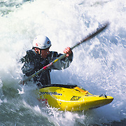 Kayaker in yellow kayak makes a run through Staircase Rapids on the South Fork of the Payette River in Idaho