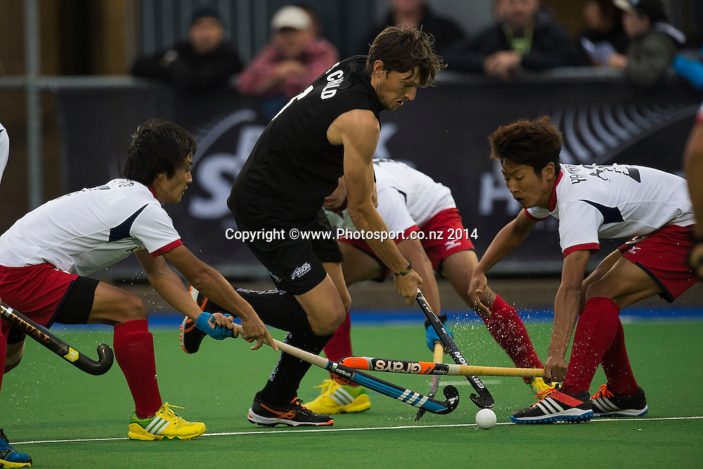 Simon Child (C captain of New Zealand is tackled by Tomonori Ono (L) and Manabu Yamashita of Japan during the Black Sticks Men v Japan international hockey match at the Coastlands Kapiti Sports Turf in Paraparaumu on Friday the 21st of November 2014. Photo by Marty Melville/www.Photosport.co.nz