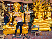 09 MARCH 2016 - BANGKOK, THAILAND: Workers on Thanon Bamrung Muang in Bangkok put the finishing touches on a large Buddhist statue that is for sale. The street is lined with workshops that make statues of the Buddha and revered Thai Buddhist monks. Once located just outside Bangkok's city walls, it's now in the heart of the city.    PHOTO BY JACK KURTZ