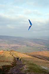 Walkers watch a hang glider launched from Mam Tor also known as Mother Hill or shivering Mountain near Castleton in the High Peak of Derbyshire, England..www.pauldaviddrabble.co.uk.15 January 2012.Image © Paul David Drabble