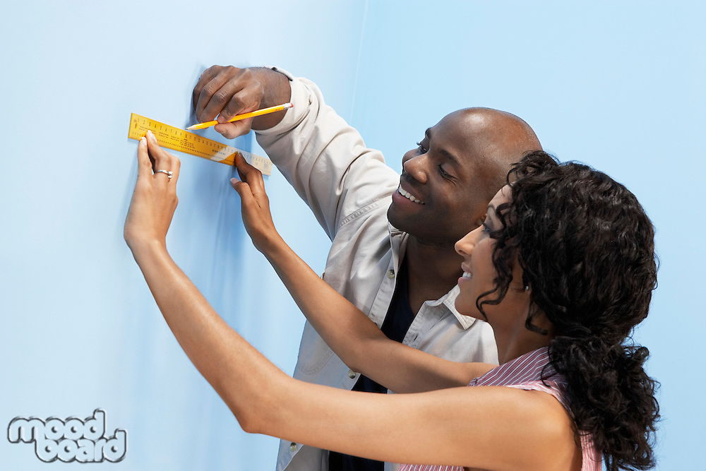 Couple measuring and marking interior wall