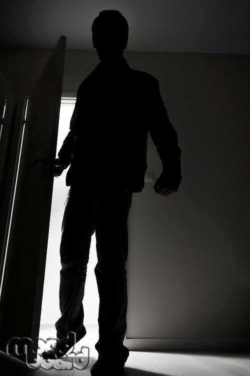 Full-length of burglar breaking into house