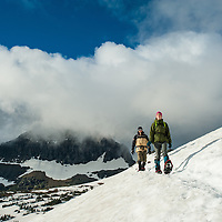 man woman snowshoeing in mountains glacier national park