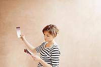 Woman looking at paint colour swatches in unrenovated room