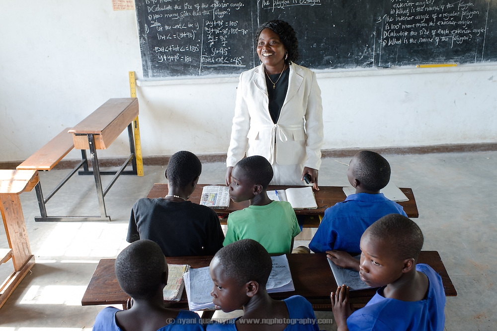Sarah Angwech, a teacher at Agwait Primary School near Tororo in Eastern Uganda, speaking to a class of boys and girls about menstrual hygiene on 1 August 2014. The school participates in a Menstrual Health Management program supported by Plan International.