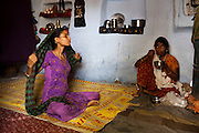 Sadma Khan (left), 19, rests at home with her family in her mother's (right) one-room house that she shares with her siblings in a slum area of Tonk, Rajasthan, India, on 19th June 2012. She was married at 17 years old to Waseem Khan, also underaged at the time of their wedding. The couple have an 18 month old baby and Sadma is now 3 months pregnant with her 2nd child and plans to use contraceptives after this pregnancy. She lives with her mother since Waseem works in another district and she can't take care of her children on her own. Photo by Suzanne Lee for Save The Children UK