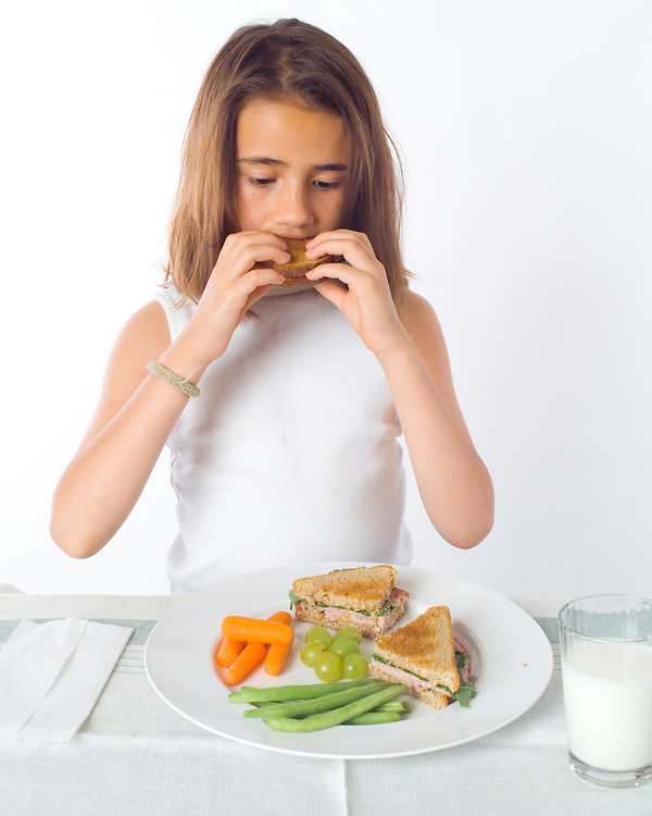 Chemical energy from food.  Girl eating sandwich with fruit, vegetables, glass of milk.