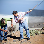 Hugo Streeter and Juan Olguin Cabezaz  from a fog collecting co-operative adjust the cable of a large fog collecting net in the Atacama Chanaral, Chile