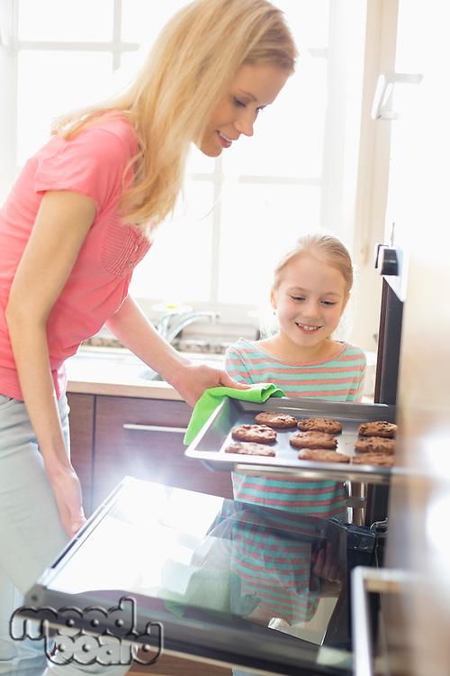 Happy mother and daughter removing cookie tray from oven at home