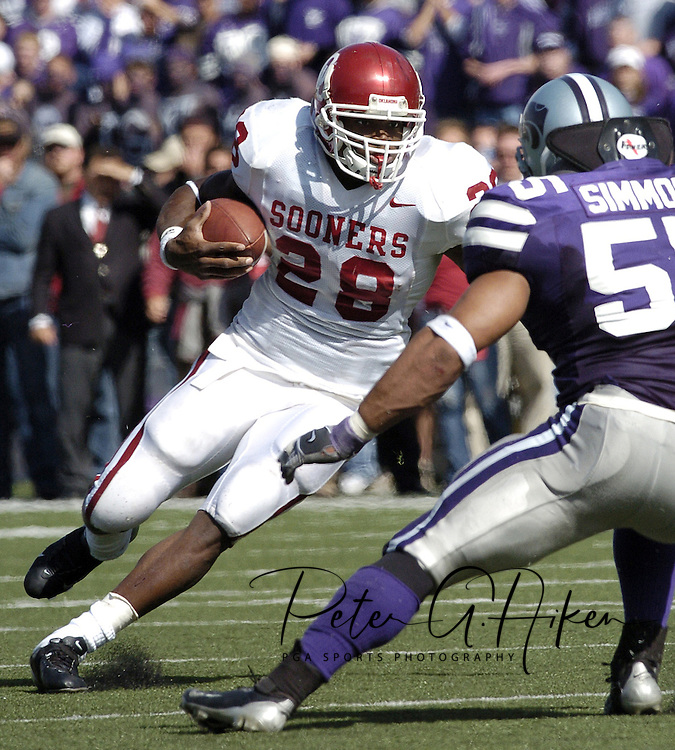 Oklahoma running back Adrian Peterson (28) rushes up field against Marvin Simmons (55) of Kansas State, during the Sooners 31-21 win at KSU Stadium in Manhattan, Kansas, Oct. 16, 2004.