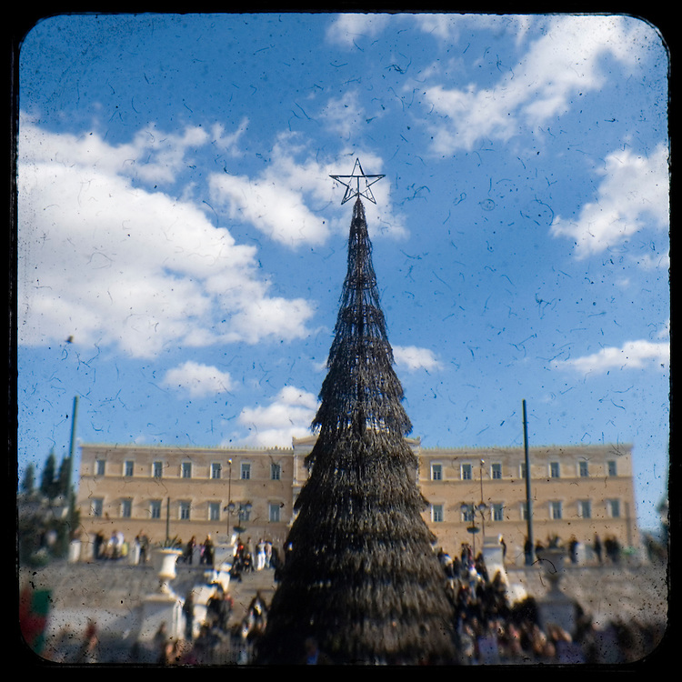 The burned Christmas tree in front of the greek parliament in Syntagma square. <br /> <br /> The killing of the 15 year old boy Alexandros Grigoropoulos by a policeman resulted in widespread riots that altered the city landscape. When I walked in the streets of my town the day after the riots I instantly forgot the image I had about Athens, that of a bustling, peaceful, energetic metropolis and in my mind came the old photographs from WWII, the civil war and the students uprising against the dictatorship. Thus I decided not to turn my digital camera straight to the destroyed buildings but to photograph through an old camera that worked as a filter, a barrier between me and the city.