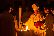 DENVER, CO - APRIL 19: Archbishop Samuel J. Aquila lights the eternal candle as John Brooks, right, and Deacon Jason Wunsch, left, look on during the Easter Vigil Mass at the Cathedral Basilica of the Immaculate Conception on April 19, 2014, in Denver, Colorado. (Photo by Daniel Petty/Denver Catholic Register)