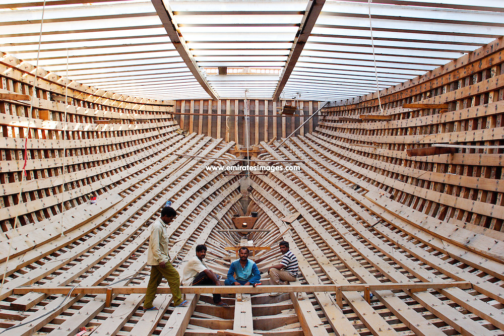 Craftsmen inside the wooden hull of a newly constructed trading dhow in Dubai
