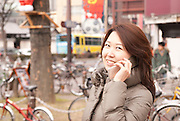 A young Japanese lady in the trendy shopping district of Sakae calling her friend, Nagoya city.