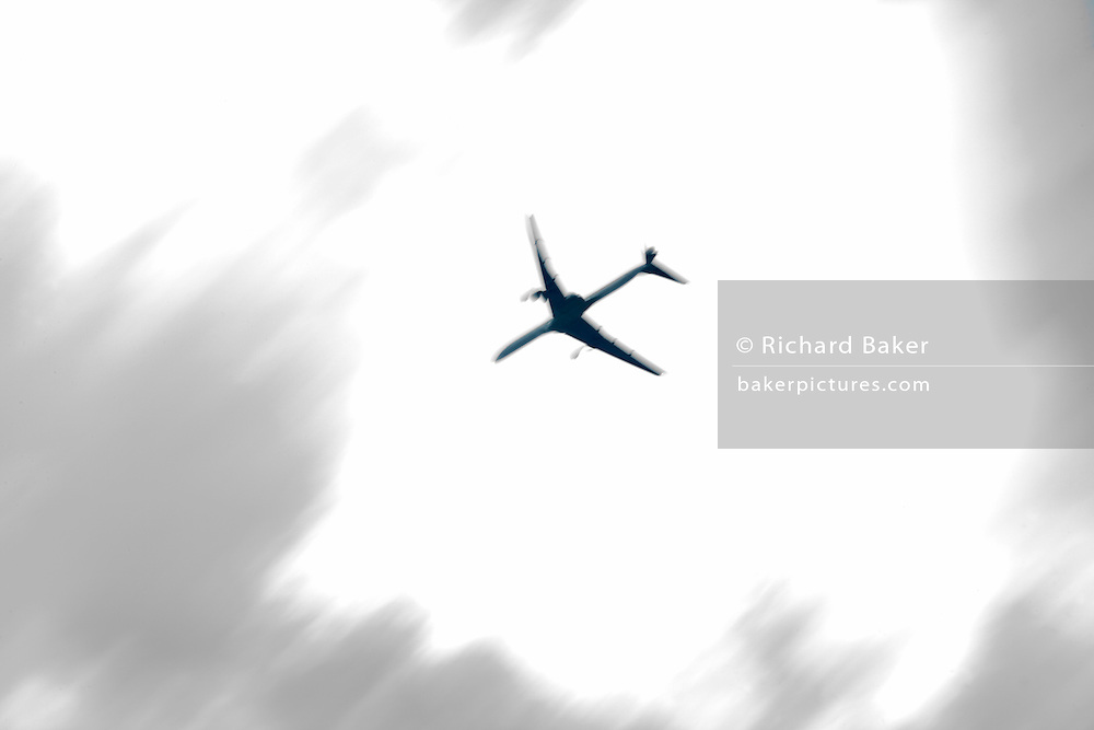 A jet airliner passes overhead in bright skies, blurred purposely using a slow camera speed.