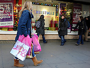 © Licensed to London News Pictures. 09/12/2011, London, UK. A woman, laden with shopping bags, walks along Oxford Street. Christmas shoppers in London's Oxford Street and Regent Street today 09 December 2011. Some of the shops are already having sales and displaying prices in windows. Photo credit : Stephen Simpson/LNP