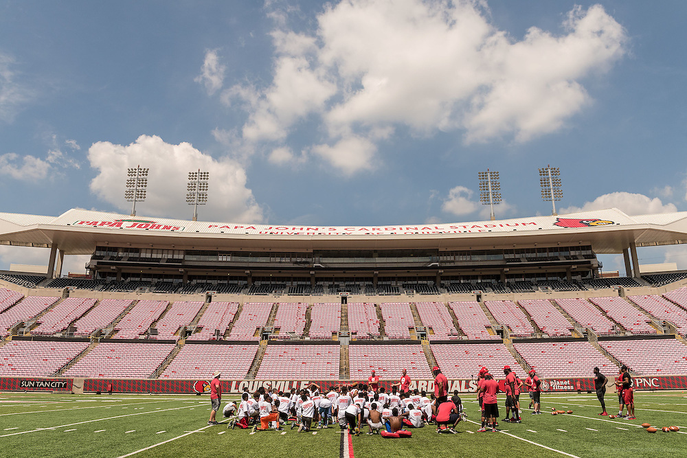 Breno Giacomini and Gary Barnidge, co-founders of the American Football Without Barriers youth football camp, speak to students gathered before lunch break at the University of Louisville's Papa John's Cardinal Stadium. June 25, 2016