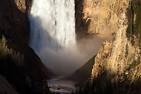 The first rays of daylight hit the Lower Falls of the Yellowstone River and the walls of the Grand Canyon at sunrise in Yellowstone National Park.