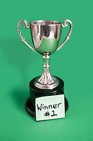 Trophy with sticky note for winner over colored background