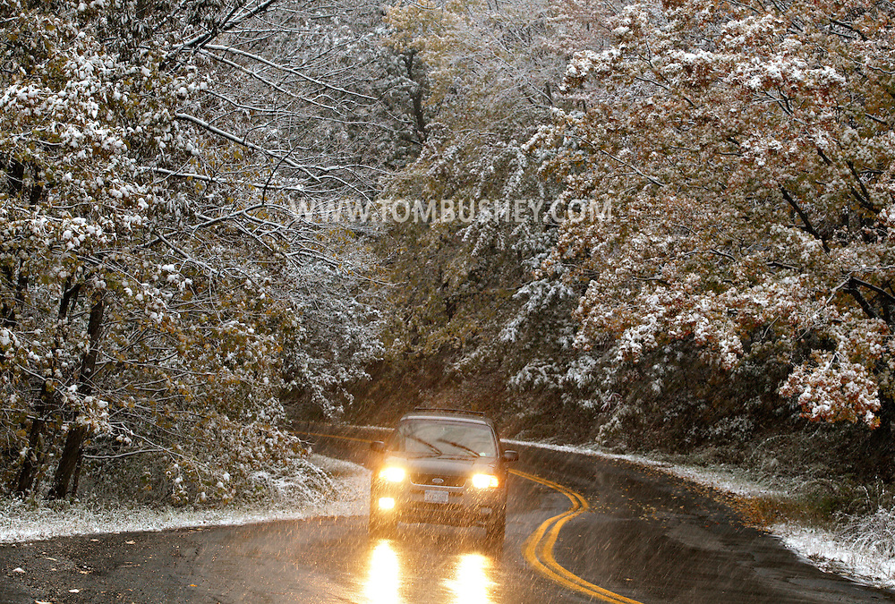 Middletown, NY - A car drives up a winding road as falling snow covers the trees during a storm onon Oct. 15, 2009.