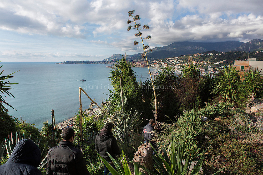 VENTIMIGLIA, ITALY - 20 NOVEMBER 2014: Refugees from Syria and Eritrea enter a trail near the Italian-French border  in Ventimiglia, Italy, on November 20th 2014. They had first tried to cross the border by train in the morning, but were caught by the French police that pushed them back to the Italian border.<br /> <br /> The Ventimiglia-Menton border is the border between Italy and France crossed by migrants who decide to continue their journey up north towards countries such as Germany, Sweden, The Netherlands and the UK where the process to receive the refugee status or humanitarian protection is smoother and faster. in Ventimiglia, Italy, on November 17th 2014.