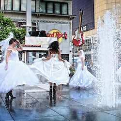 Brides dance a lovely ballet among water fountains in the heart of downtown Toronto, Canada.