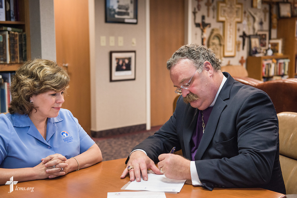 LCMS President Rev. Dr. Matthew C. Harrison signs a Memorandum of Understanding Wednesday, May 14, 2014, with Patti Garibay, national executive director of American Heritage Girls, at the International Center of The Lutheran Church--Missouri Synod in Kirkwood, Mo.  LCMS Communications/Erik M. Lunsford