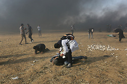 Medics treat a Palestinian suffering from teargas inhalation during clasheswith Israeli soldiers at the border fence with Israel east of Khan Yunis in the southern Gaza Strip, Israeli soldiers killed at least 60 Palestinians and wounded more than 2,700. as demonstrations on the Gaza-Israel border coincided with the controversial opening of the U.S. Embassy in Jerusalem. This marks the deadliest day of violence in Gaza since 2014. Gaza's Hamas rulers have vowed that the marches will continue until the decade-old Israeli blockade of the territory is lifted. Gaza Strip, Palestine, May 15, 2018. Photo by Ashraf Amra/SalamPix/ABACAPRESS.COM