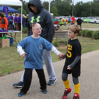 Libby Ezell | BUY at PHOTOS.DJOURNAL.COM<br /> Peyton Knight, left, walks with his older brother Chandler Knight, behind, and his friend John Eli Tull at Saturday's Buddy Walk