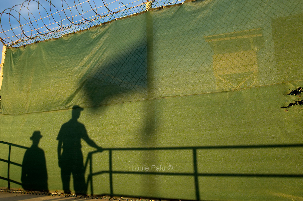 """The shadows of military officials and a flag are seen cast on a fence in Camp Delta at the detention facility in Guantanamo Bay, Cuba. Approximately 250 """"unlawful enemy combatants"""" captured since the September 11, attacks on the United States continue to be held at the detention facility.(Image reviewed by military official prior to transmission)"""