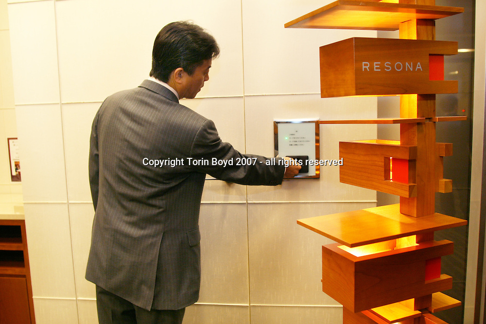 This is the high tech automated safe deposit box system in use by Resona Bank, Ltd. of Japan. Although this concept was thought up by the bank, it was jointly developed by Resona, NTT DATA Corporation, and Itoki Corporation. What makes it unique is that uses an IC cash card with biometric authentication that is used as a key by customer to access their safe deposit boxes. It is seen here being demonstrated at Resona's Tokyo Midtown branch by the branch General Manager Katsuhiko Makino. Resona opened this branch in March 2007 in the trendy building complex called Tokyo Midtown, located in the Roppongi district of central Tokyo. Photo taken Nov. 15, 2007.