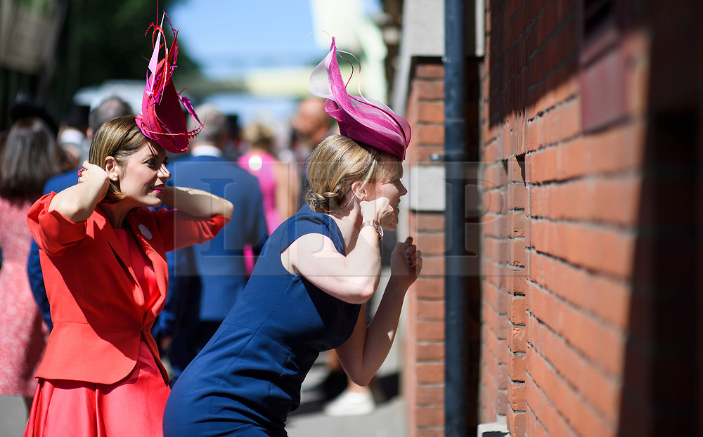 © Licensed to London News Pictures. 21/06/2018. London, UK. Two Racegoers adjust their hats in a window reflection at Ladies Day at Royal Ascot at Ascot racecourse in Berkshire, on June 21, 2018. The 5 day showcase event, which is one of the highlights of the racing calendar, has been held at the famous Berkshire course since 1711 and tradition is a hallmark of the meeting. Top hats and tails remain compulsory in parts of the course. Photo credit: Ben Cawthra/LNP