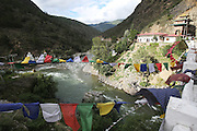 Three rivers converge from India, Nepal and the Himalayas. Bhutan relies hevily on the export of hydro-electric power. Paro, Bhutan..Bhutan the country that prides itself on the development of 'Gross National Happiness' rather than GNP. This attitude pervades education, government, proclamations by royalty and politicians alike, and in the daily life of Bhutanese people. Strong adherence and respect for a royal family and Buddhism, mean the people generally follow what they are told and taught. There are of course contradictions between the modern and tradional world more often seen in urban rather than rural contexts. Phallic images of huge penises adorn the traditional homes, surrounded by animal spirits; Gross National Penis. Slow development, and fending off the modern world, television only introduced ten years ago, the lack of intrusive tourism, as tourists need to pay a daily minimum entry of $250, ecotourism for the rich, leaves a relatively unworldly populace, but with very high literacy, good health service and payments to peasants to not kill wild animals, or misuse forest, enables sustainable development and protects the country's natural heritage. Whilst various hydro-electric schemes, cash crops including apples, pull in import revenue, and Bhutan is helped with aid from the international community. Its population is only a meagre 700,000. Indian and Nepalese workers carry out the menial road and construction work.