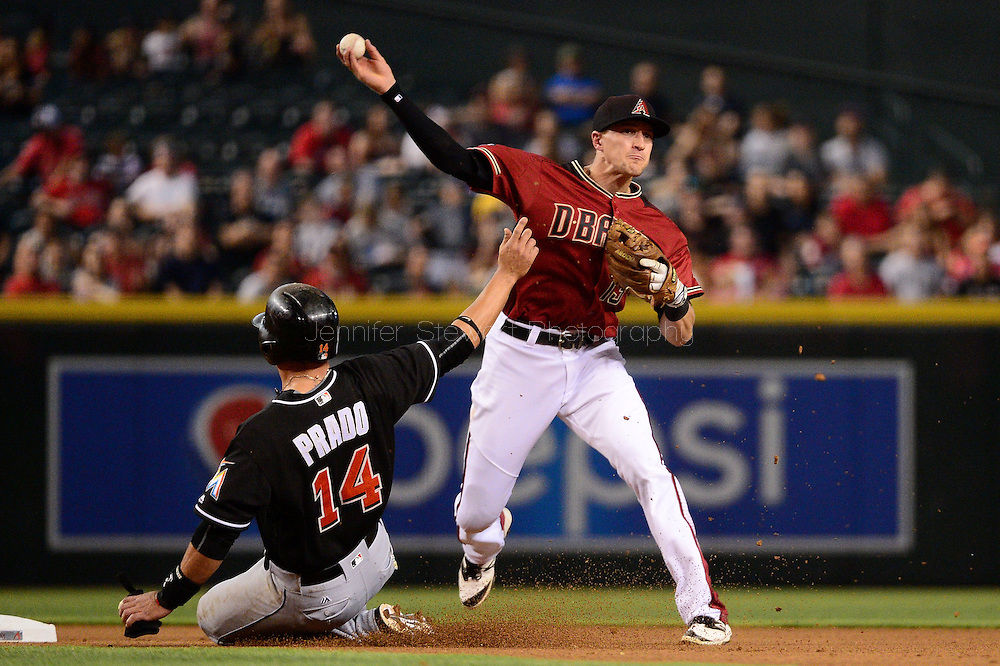 PHOENIX, AZ - JUNE 12:  Nick Ahmed #13 of the Arizona Diamondbacks turns the double play over the sliding Martin Prado #14 of the Miami Marlins in the fourth inning at Chase Field on June 12, 2016 in Phoenix, Arizona.  (Photo by Jennifer Stewart/Getty Images)