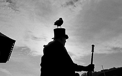 © Licensed to London News Pictures.01/11/15<br /> Whitby, UK. <br /> <br /> A man wearing a top hat with a raven on top poses for pictures as hundreds of visitors attend the Whitby Goth weekend in Whitby, North Yorkshire. The event began in 1994 to celebrate goth culture and music and takes place twice each year. <br /> Thousands of extravagantly dressed people attend the popular event wearing Steampunk, Cybergoth, Romanticism, Victoriana and other clothing as they take part in the celebration of Goth culture. <br /> <br /> Note to Editors - Picture shot on Kodak Tri X 400ISO film.<br /> Photo credit : Ian Forsyth/LNP