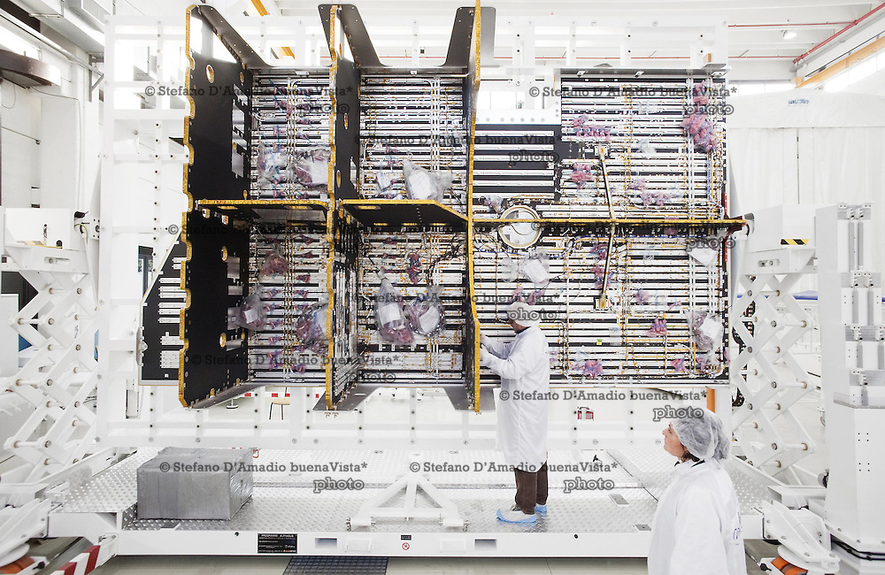 Mechanical integration room with technicians busy at work on a Repeat Module of the first Alphasat telecommunications satellite. Alphastat is the largest satellite in<br />  the world.