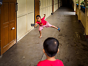 28 JANUARY 2018 - LEGAZPI, ALBAY, PHILIPPINES: Boys play badminton using their shoes as paddles at the evacuation shelter for people from Barangay (community) Matanag in Albay Central School in Legazpi. People from the community have been in the shelter since Mayon volcano started erupting two weeks ago. There are about 500 families at the shelter, around 2,000 people. More than 80,000 people have been evacuated from communities around the volcano and are living in shelters and camps outside of the evacuation zone. The Philippine government is preparing to house the people for up to three months.      PHOTO BY JACK KURTZ