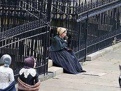 "Moray Place in Edinburgh's Georgian old town was turned into 19th century London for Julian Fellowes' new ITV show ""Belgravia"".<br /> <br /> Pictured: An actress dressed as a maid checks her boots are laced up correctly but has to make some adjustments before she runs along the street. Here she takes a breather between takes.<br /> <br /> Alex Todd 