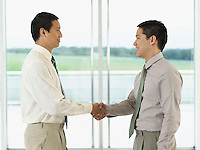 Businessmen standing Shaking Hands in front of window profile