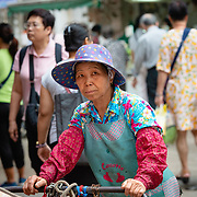 Woman with delivery cart at a street market in Hong Kong
