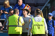 An Oldham fan in his Rainbow coloured Top Hat chats to Stewards during the EFL Sky Bet League 1 match between Northampton Town and Oldham Athletic at Sixfields Stadium, Northampton, England on 5 May 2018. Picture by Dennis Goodwin.